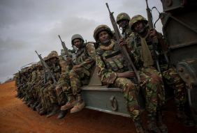 Soldiers of the Kenyan Contingent serving the AMISOM sit in a truck as their convoy makes its way between the port of Kismayu and the city's airport
